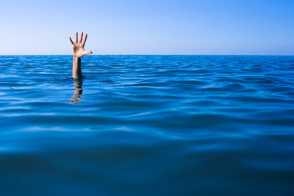 Help needed. Drowning man's hand in sea or ocean.