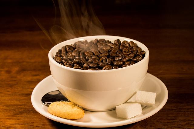 auf-diesem-bild-ist-eine-weisse-tasse-gefüllt-mit-dampfenden-kaffeebohnen.png