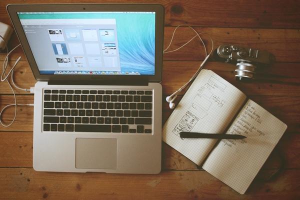 hier liegt ein schreibheft neben einem laptop