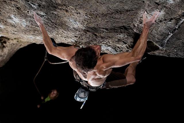 Mann klettert am Fels