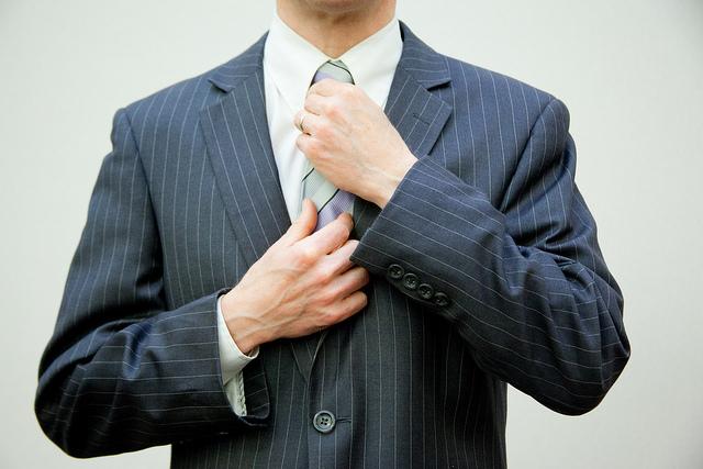 Mann im Anzug fasst sich an die Krawatte