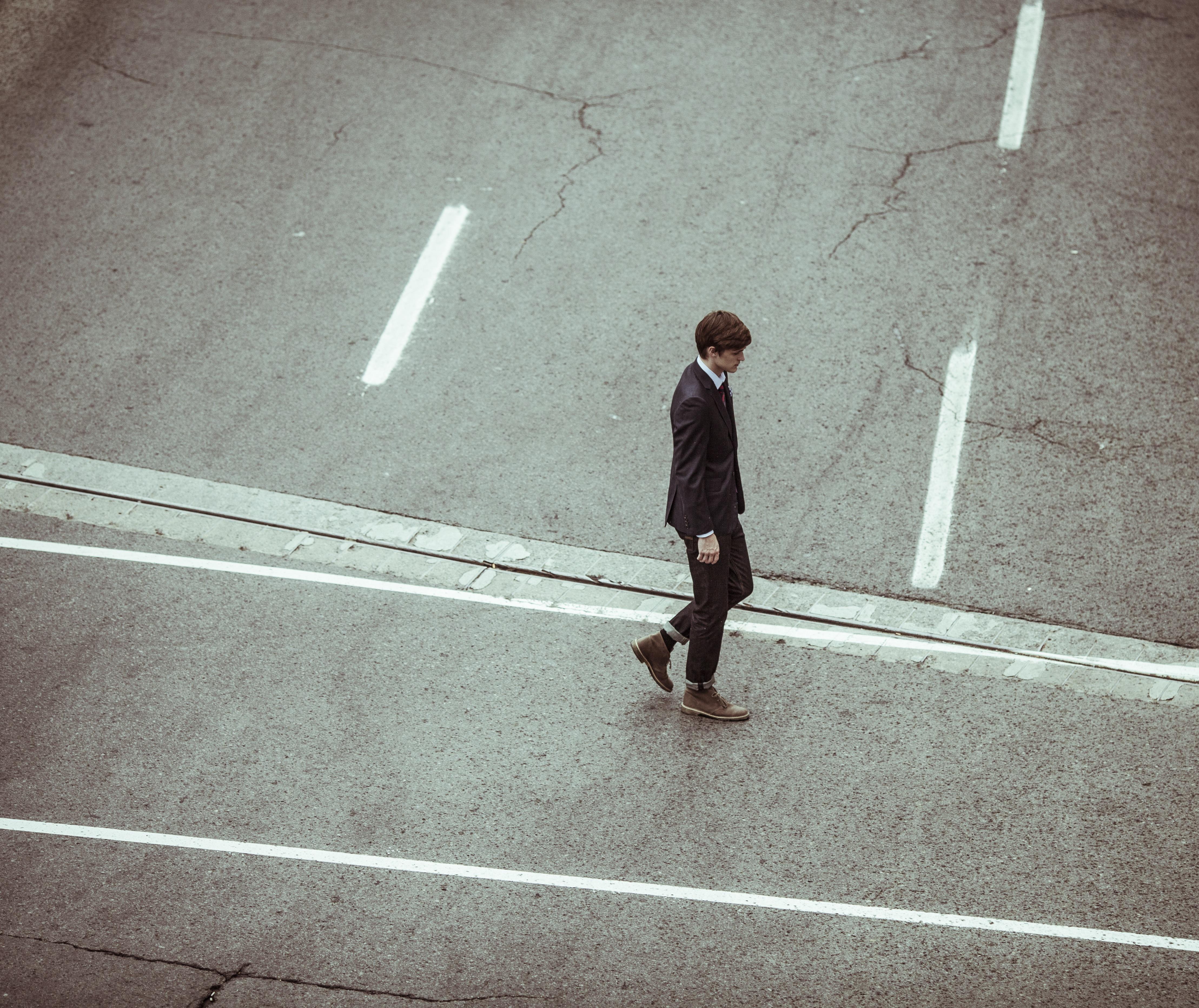 Mann im Anzug läuf allein über Straße