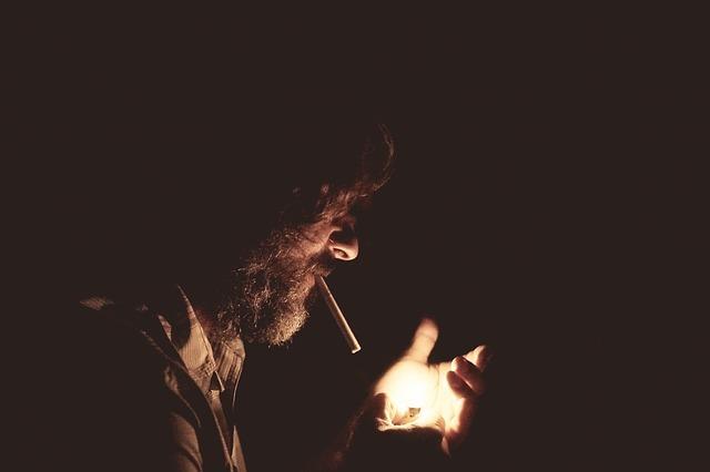 Mann im Dunkel brennt sich eine Zigarette an