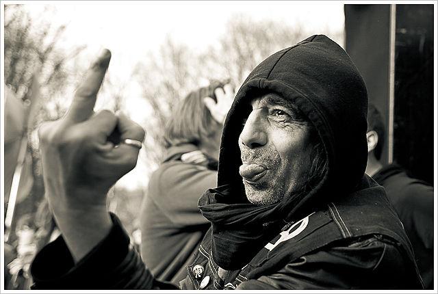 Mann zeigt Mittelfinger und streckt die Zunge raus