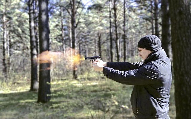 Mann feuert Schuss im Wald ab