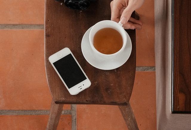 das sind ein smartphone und eine tasse tee auf einem tisch